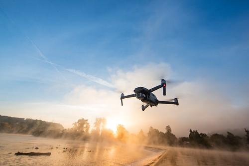 Drone copter with digital camera, river with fog on background. Modern technology, UAV concept