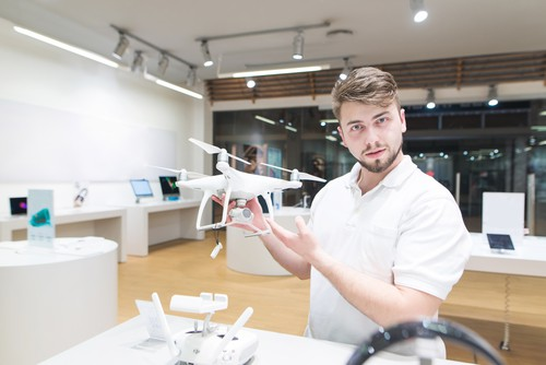 Handsome man stands with a quadcopter in his hands at a modern store and looks at the camera. Buy quadcopter at the drones store