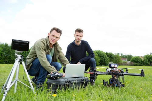 two people who are practicing on how to fly a drone for photography