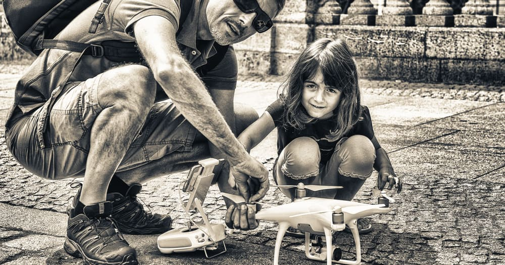 Man in 40s showing his daughter how to setup his drone for flyin