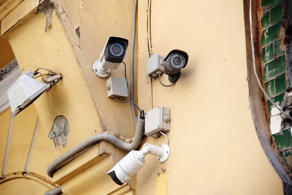 three outdoor video cameras on an old beige building