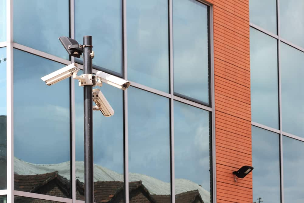three security camera against finance building with reflections