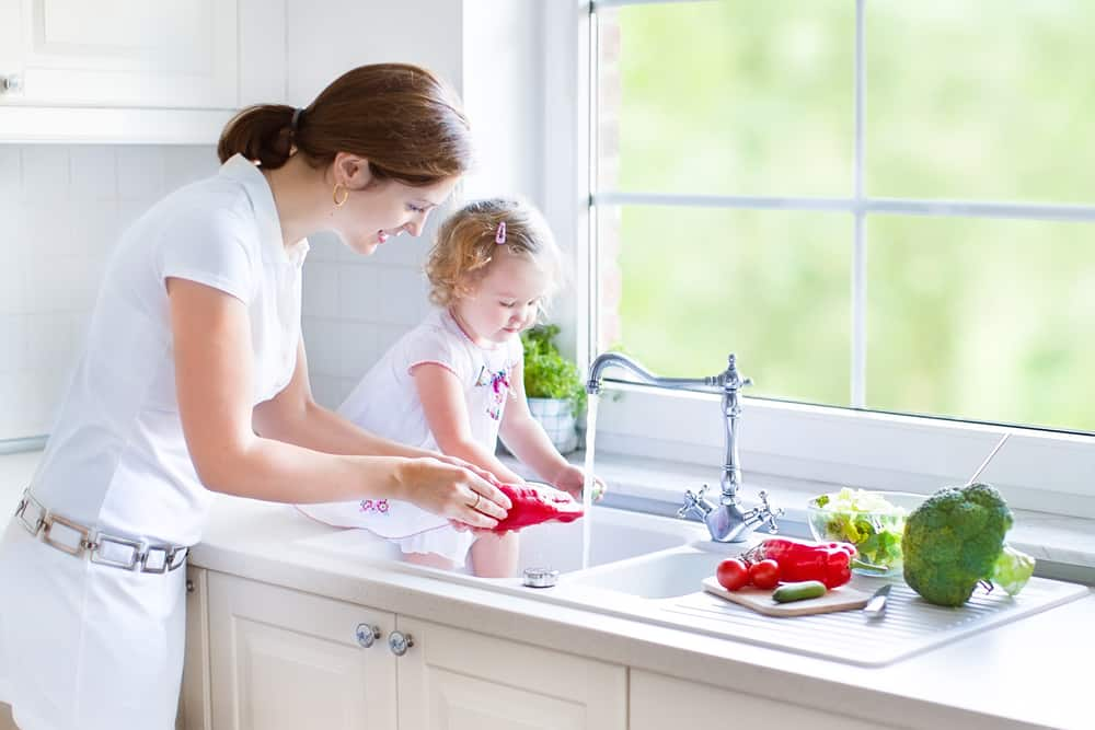 Mother and her daughter washing vegetables with a water heater under the sink
