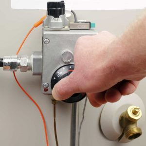 Hand of a man turning down household gas water heater temperature.