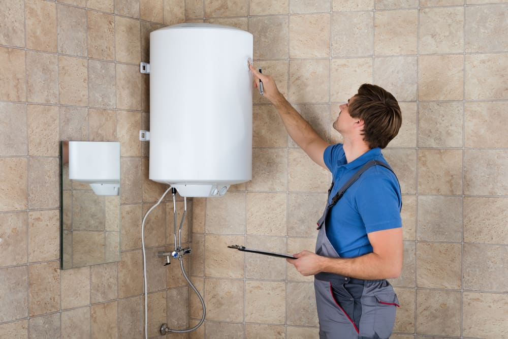 Male Plumber Holding Clipboard Checking Electric Boiler