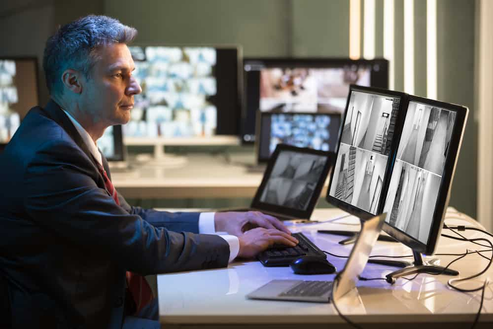 Side View Of A Mature Businessman Looking At CCTV Camera Footage On Multiple Computer Screen