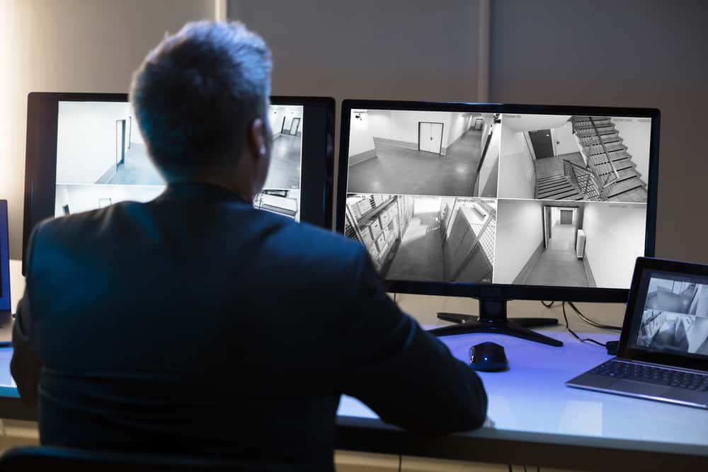 Side View Of A Mature Businessman Looking At a Long Range CCTV Camera Footage On Multiple Computer Screen