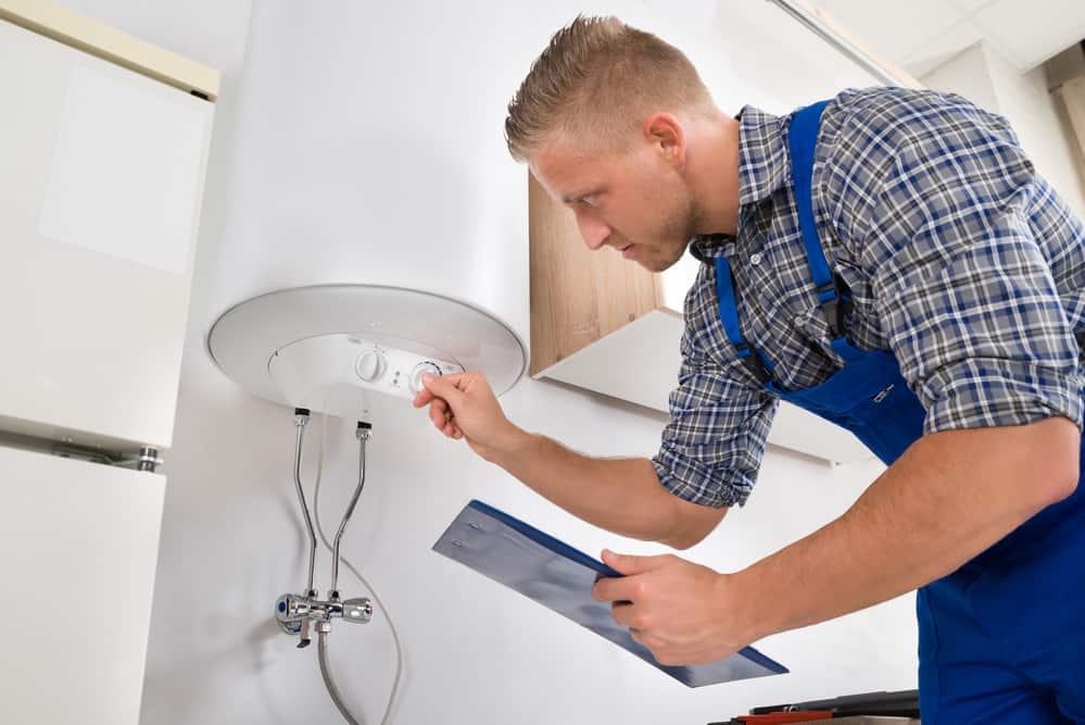 Worker Adjusting Temperature Of Water Heater
