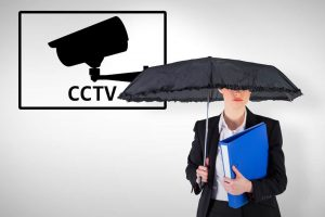 Businesswoman holding a black umbrella against cctv policy and privacy