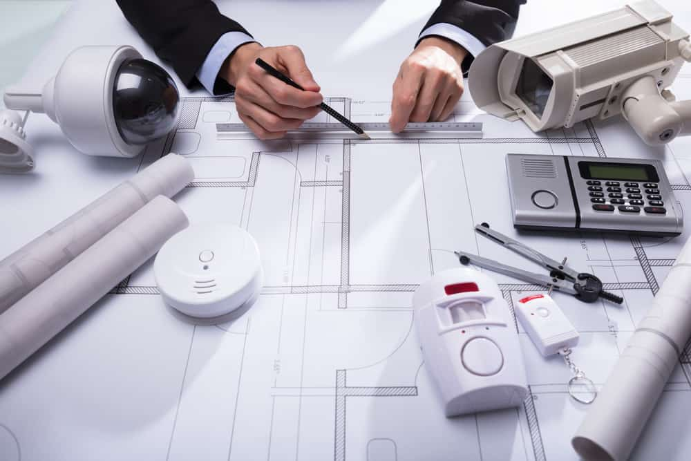 Close-up Of An Architect's Hand Drawing Blueprint With Security Equipments On Desk