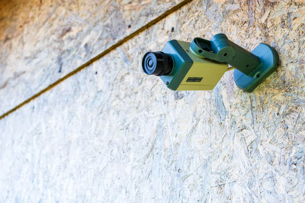 Fake security camera placed on a wooden OSB (oriented strand board) in sub-urban neighborhood