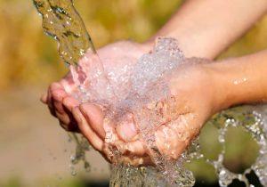 Woman's hands with rain water splash
