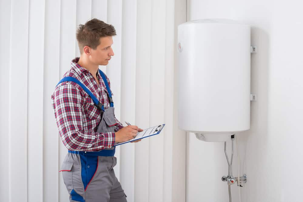 Young Male Plumber Holding Clipboard Checking Electric Water Heater