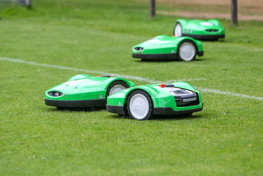 Automatic robotic lawnmower on green grass in the stadium