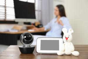 Baby monitor, camera with toy on table and woman working in home office. Video nanny