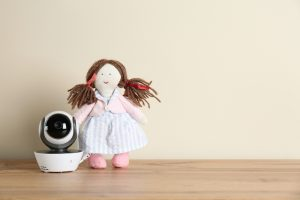 Baby monitor with camera on table against white wall