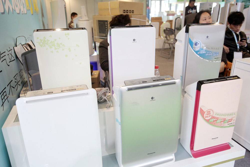 Customers shop for air purifiers at a home appliance store