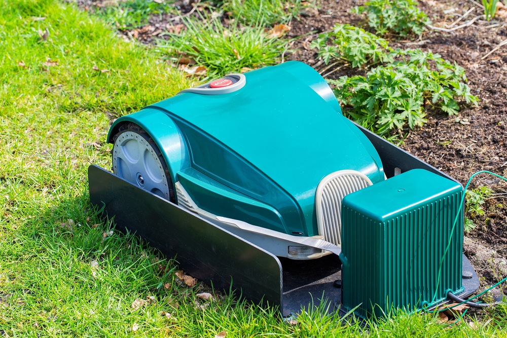 Green electric robotic Lawnmower charging on grass