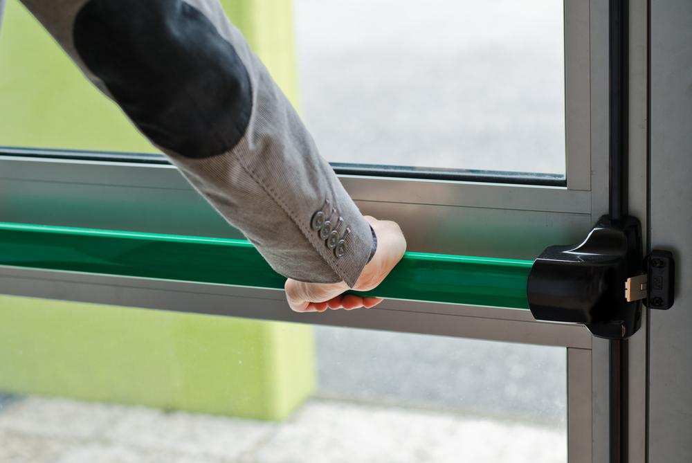 Hand pressing panic push bar to open door