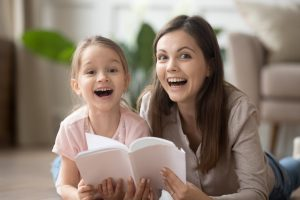 Smiling nanny and a child lying on floor reading book together
