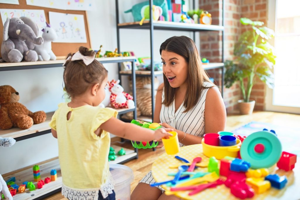 Young beautiful nanny and toddler playing with dishes, cutlery and cups toy on the table at kindergarten