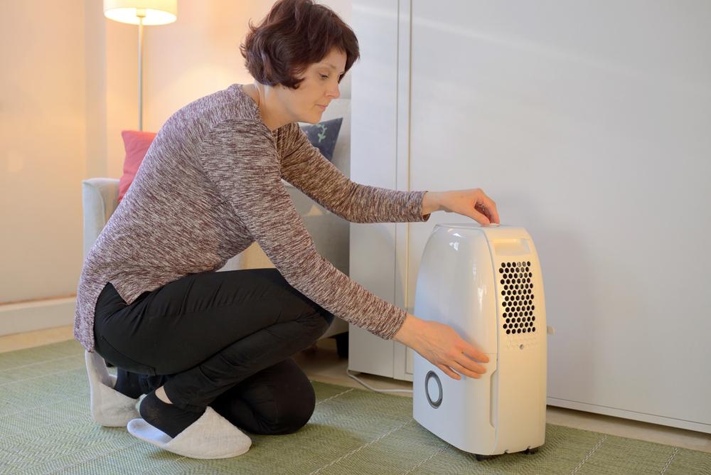 a old woman checks her small dehumidifier