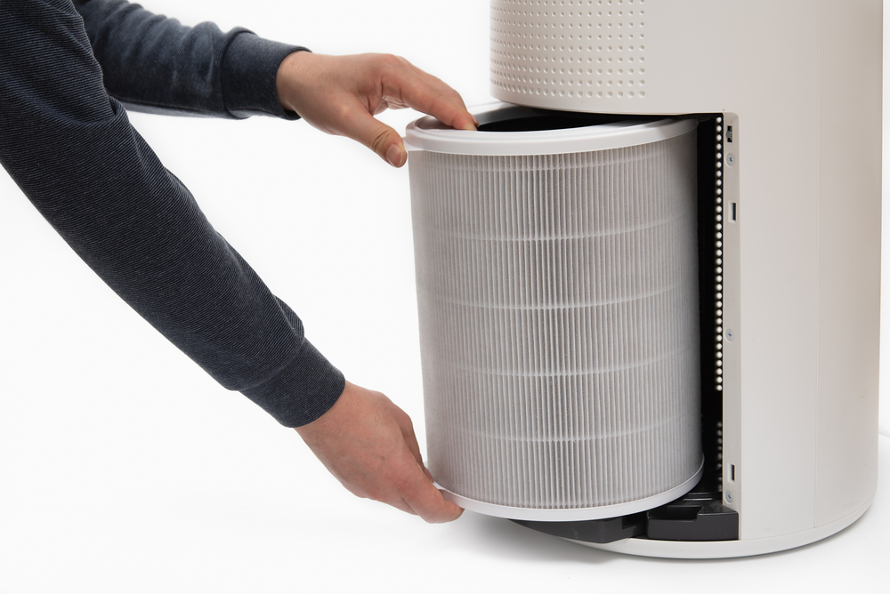 A mans hand turning an air purifiers filter into a new one