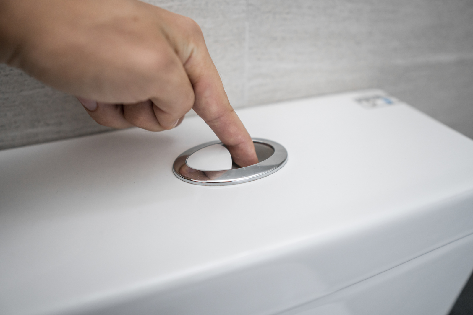 Close up of finger pushing a flush toilet button for cleaning a toilet.